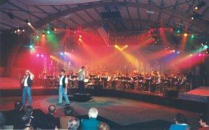 Photo du concert spectacle de 1997 présentant la scène avec 2 chanteurs et en arrière plan l'harmonie elle-même
