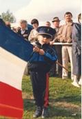Photo en couleur d'un enfant habillé en musicien tenant un drapeau français lors du festival de 1987